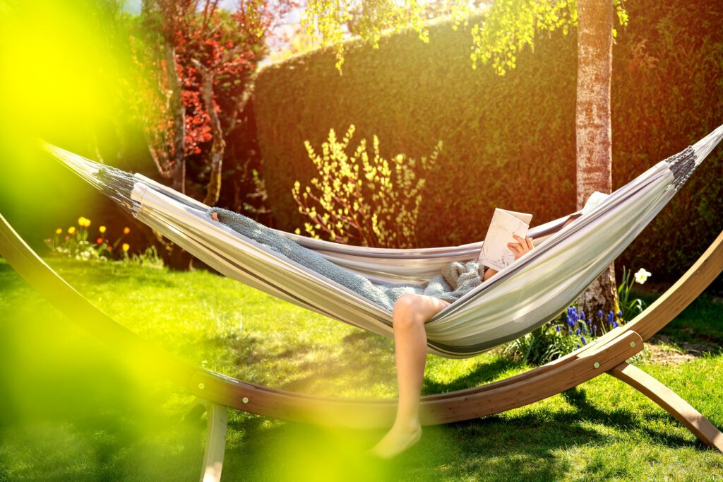 Young relaxed girl reading book in hammock in garden at home at bright sunset